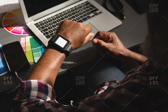 Senior graphic designer checking time on smartwatch in office