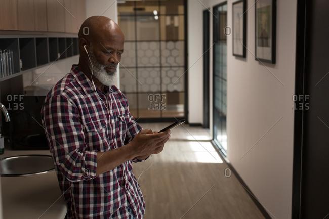 Senior graphic designer listening music on mobile phone in office