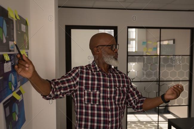 Senior graphic designer discussing over graph in office