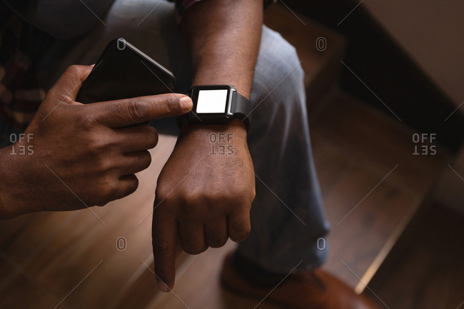 Senior graphic designer using smartwatch at stairs in office