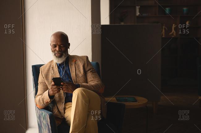 Senior graphic designer talking on mobile phone in office