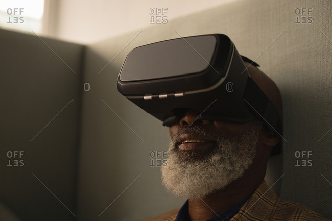Senior graphic designer using virtual reality headset in cafeteria at office