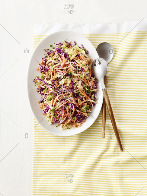 Creamy coleslaw in a white dish with serving spoons