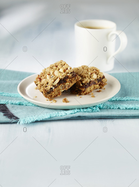 Close-up of two date squares on a plate with coffee