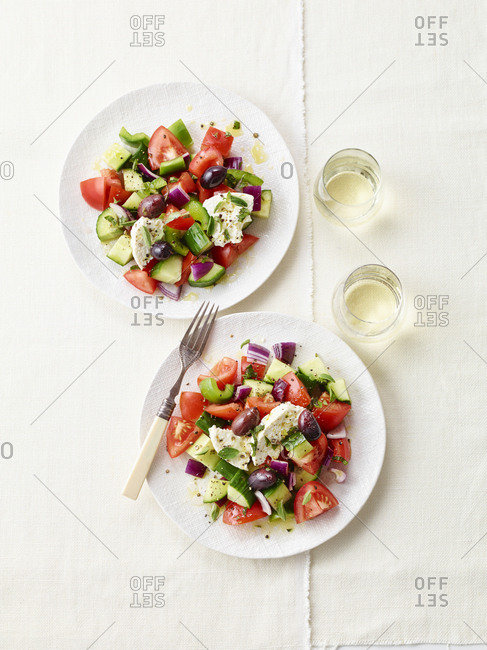 Two plates of greek salad on textured tablecloth from above