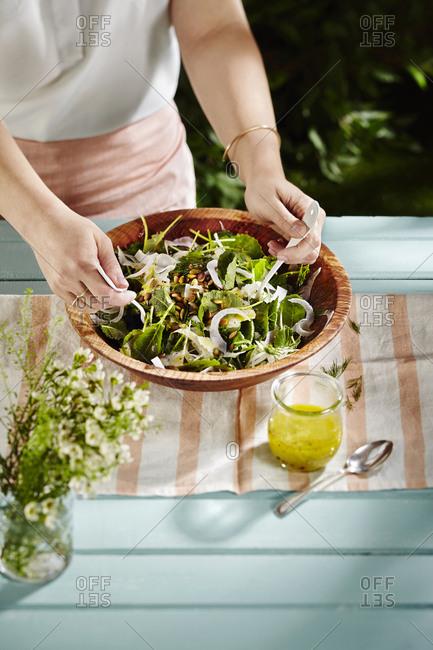 Woman preparing lemon dill summer salad at outdoor picnic table
