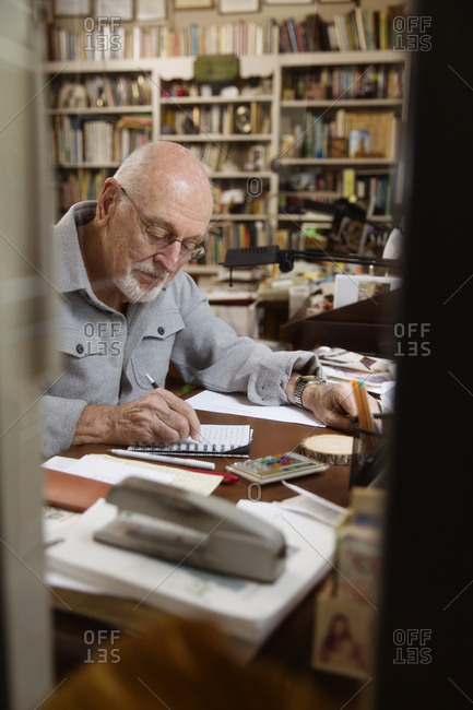 Window view of elderly man taking notes in home office.