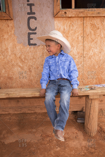 Monument Valley, Utah, USA - May 6, 2018: Smiling boy wearing cowboy hat and cowboy boots sitting on a bench