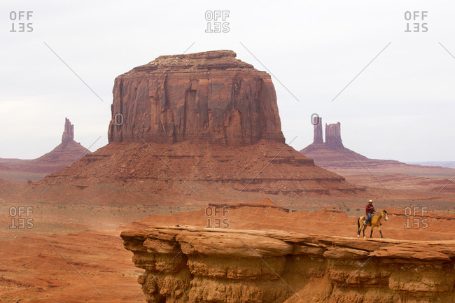 Monument Valley, Utah, USA - May 6, 2018: American Indian riding horse on mesa