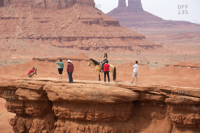 Monument Valley, Utah, USA - May 6, 2018: Tourists posing for pictures on mesa with American Indian and horse