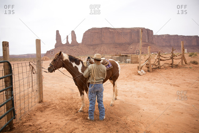 Guide saddling horses at riding stable for tourists at Monument Valley Navajo Tribal Park