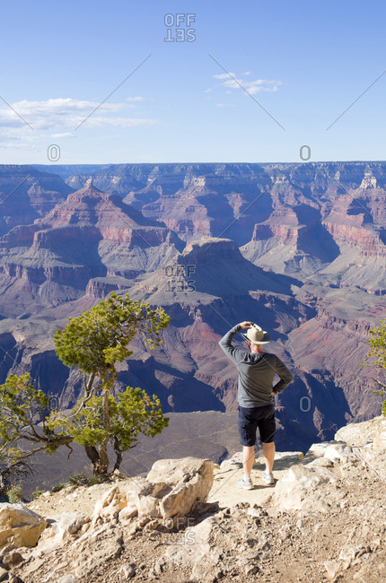 Tourist wearing cowboy hat enjoying view of the Grand Canyon