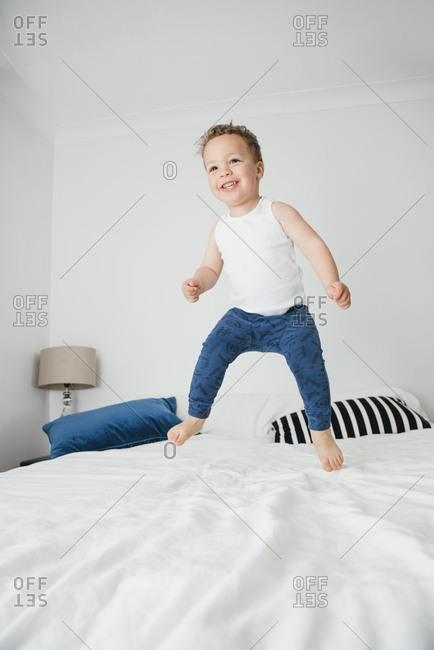 Smiling toddler jumps on bed