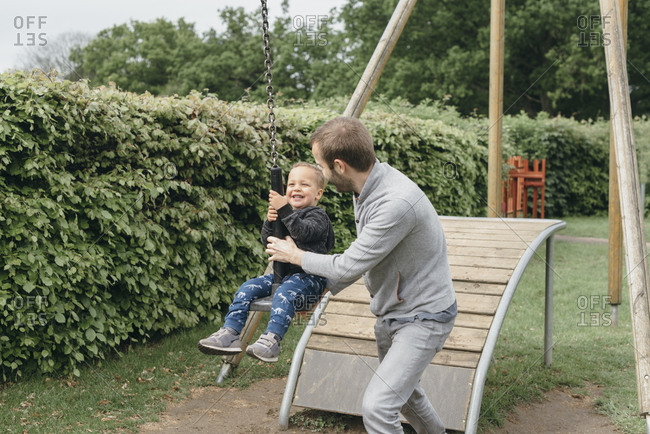 Boy on a zip line swing hold by his father