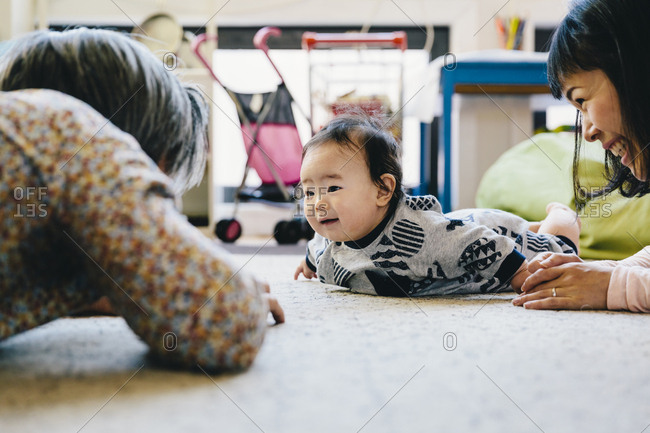 Happy mother and grandfather playing with cute baby boy lying on rug at home
