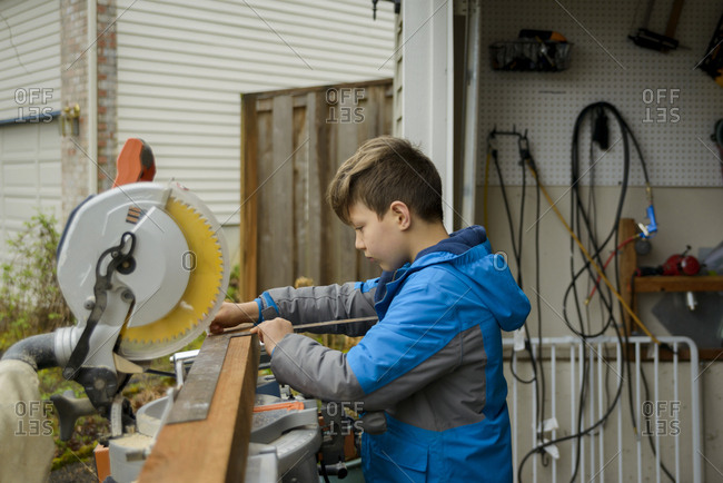 Side view of boy measuring wooden plank while working at backyard