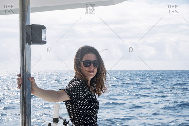 Young woman wearing sunglasses while standing in boat on sea