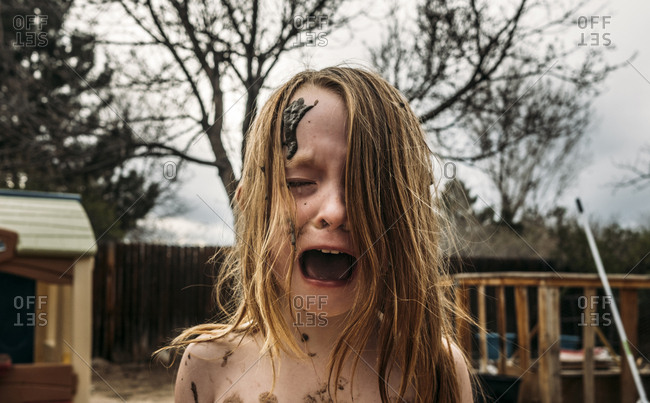 Close-up of girl crying and screaming with mud on face at backyard
