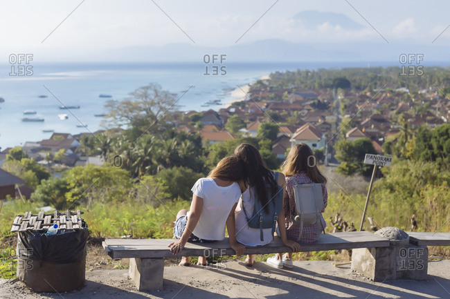 Rear view of friends looking at view while sitting on bench against sky