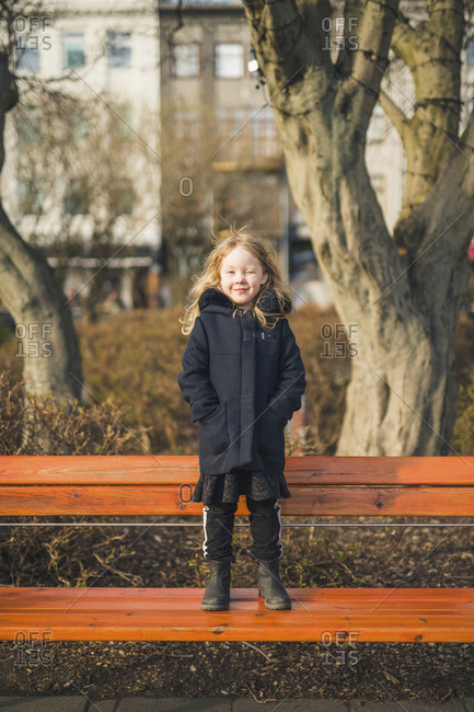 Full length portrait of girl with hands in coat's pockets winking while standing on bench at park