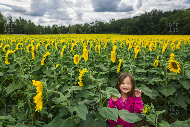 Portrait of cute happy girl standing at sunflower farm against cloudy sky