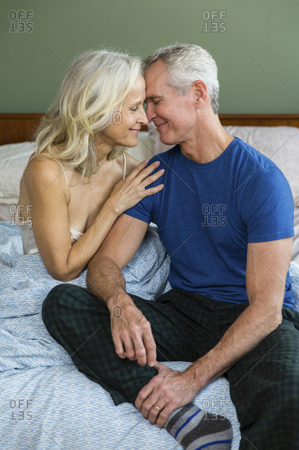 Couple romancing while sitting on bed at home