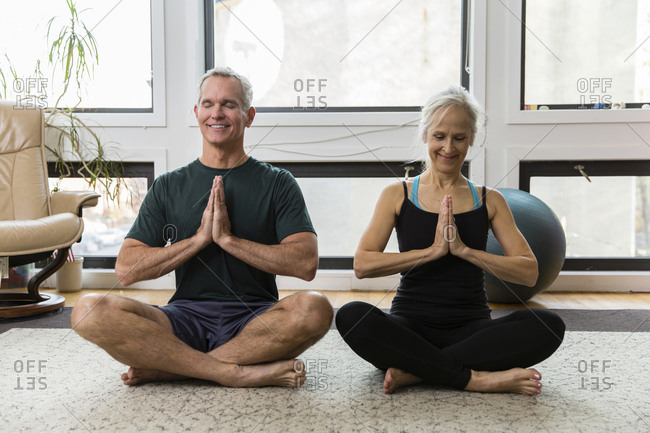Full length of couple with hands clasped meditating while exercising at home