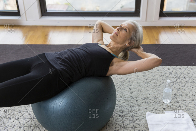 Senior woman with hands behind head lying on fitness ball while exercising at home