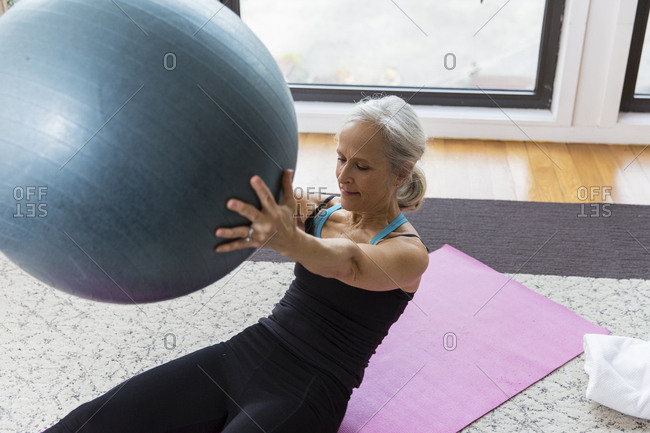 Senior woman holding fitness ball while exercising at home