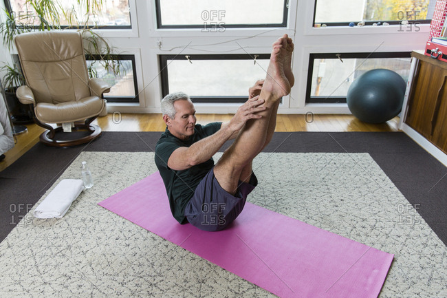 Mature man exercising on exercise mat at home
