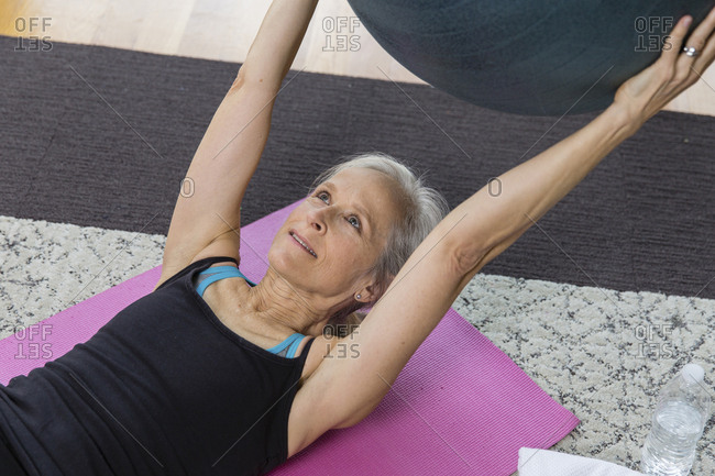 Senior woman holding fitness ball while lying on exercise mat at home