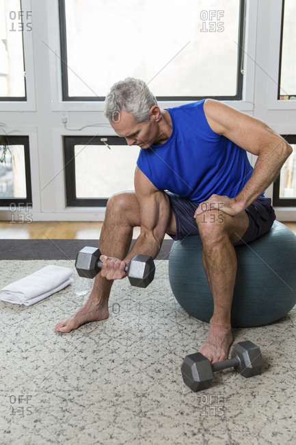 Full length of muscular mature man lifting dumbbell while sitting on fitness ball at home