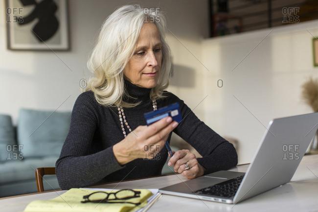 Senior woman using laptop computer while paying bills at home