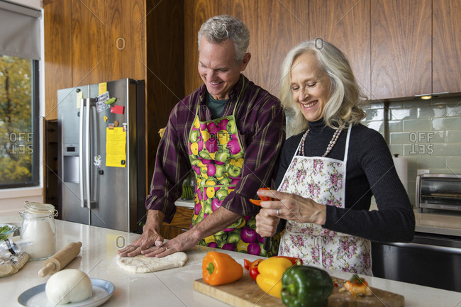 Smiling woman cutting bell pepper while man making pizza dough in kitchen at home