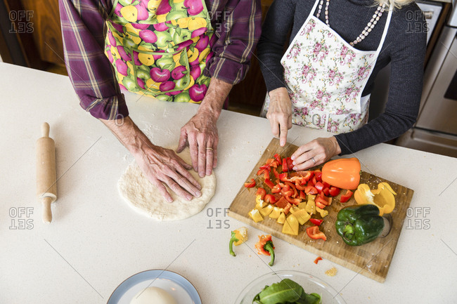 Midsection of woman cutting bell pepper while man making pizza dough in kitchen at home