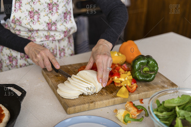 Midsection of woman cutting cheese while preparing food in kitchen at home