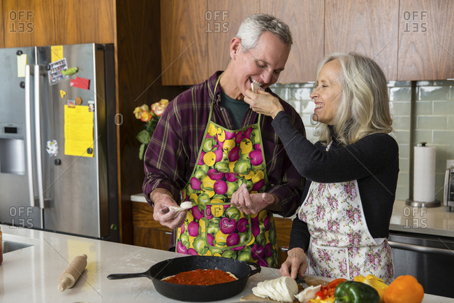 Cheerful woman feeding cheese to man while preparing food in kitchen at home