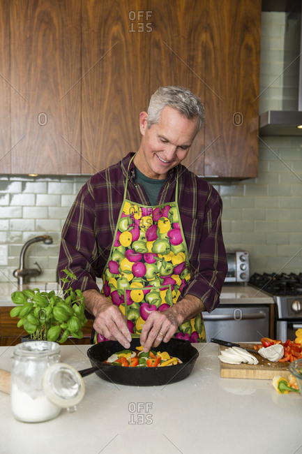 Smiling mature man preparing pizza in kitchen at home