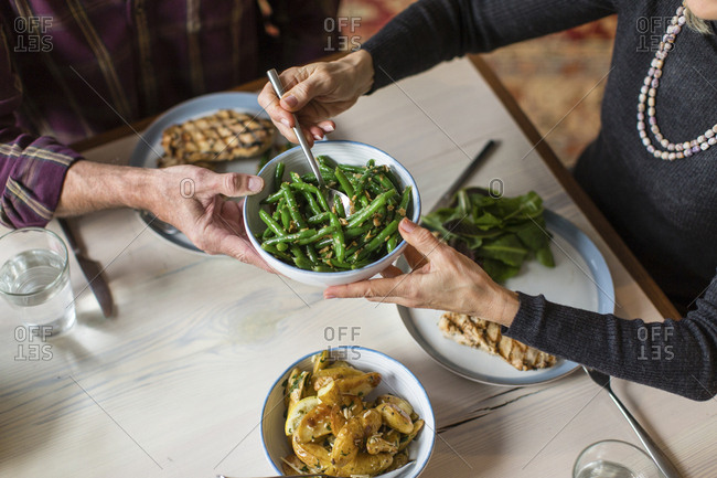 Midsection of man giving bowl of cooked green beans to woman at dining table