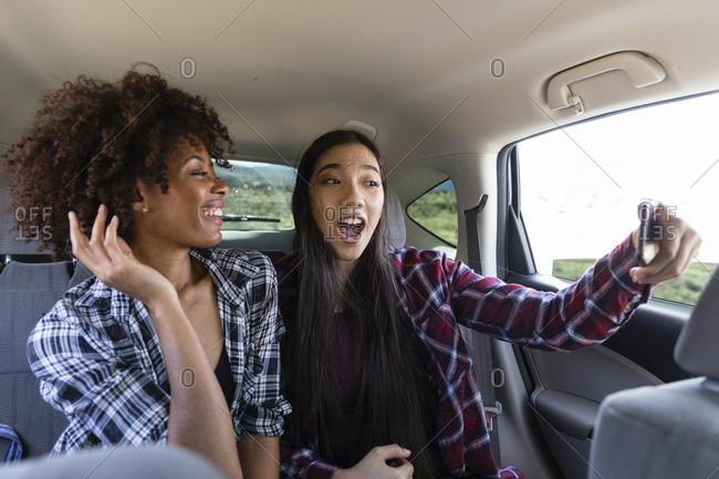 Happy female friends talking selfie while traveling in car