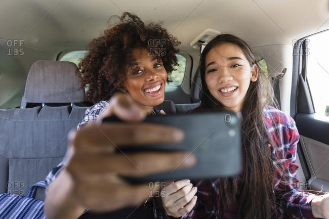 Happy friends talking selfie while traveling in car