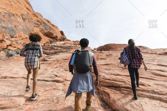 Rear view of friends hiking on rock formations against sky during sunny day