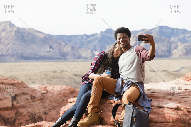 Happy friends taking selfie with mobile phone while sitting on rock formations against clear sky