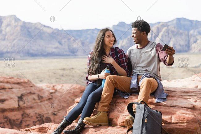 Happy friends talking while taking selfie on rock formations against clear sky during sunny day