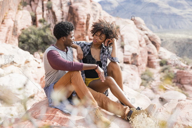 Couple looking at each other while sitting on rock formation during sunny day