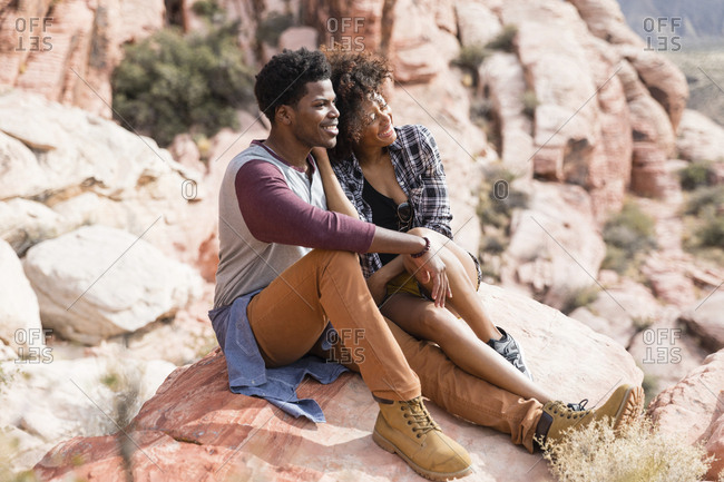 Couple looking away while sitting on rock formation during sunny day