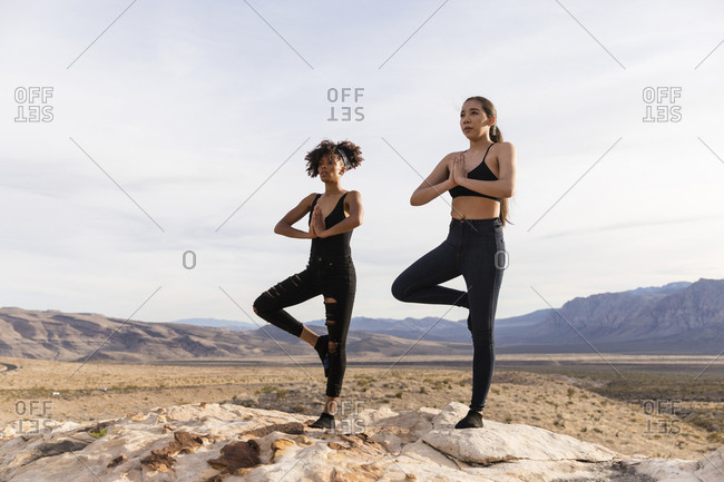 Female friends meditating while standing on rock formation against sky