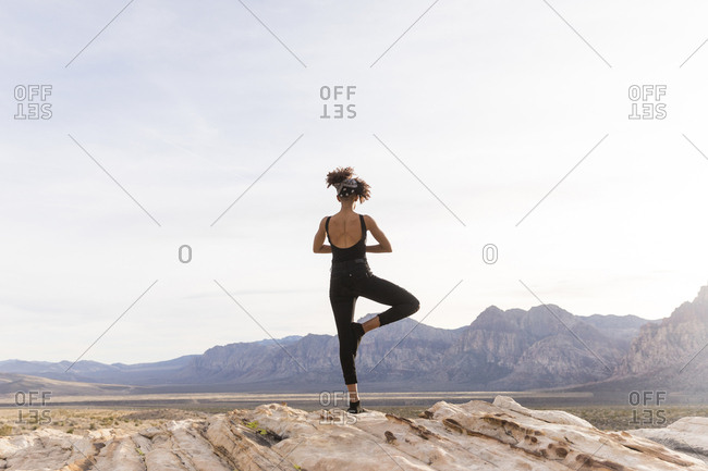 Rear view of woman meditating while standing on rock formation against sky