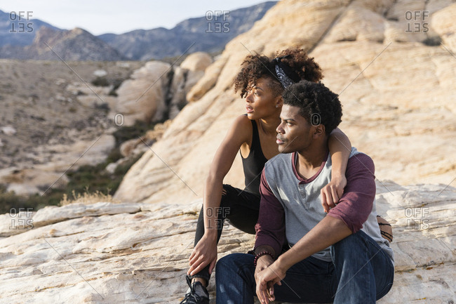 Couple looking away while sitting on rock formation