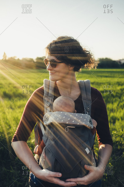 Mother carrying son in baby stroller while standing on grassy field against clear sky